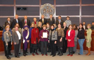 Members of TPSMA and the Fairfax Commission for Women with Edie Mayo (c) as she receives Women's History Month Proclamation from Fairfax County Board Chair Sharon Bulova (to right of Edie)